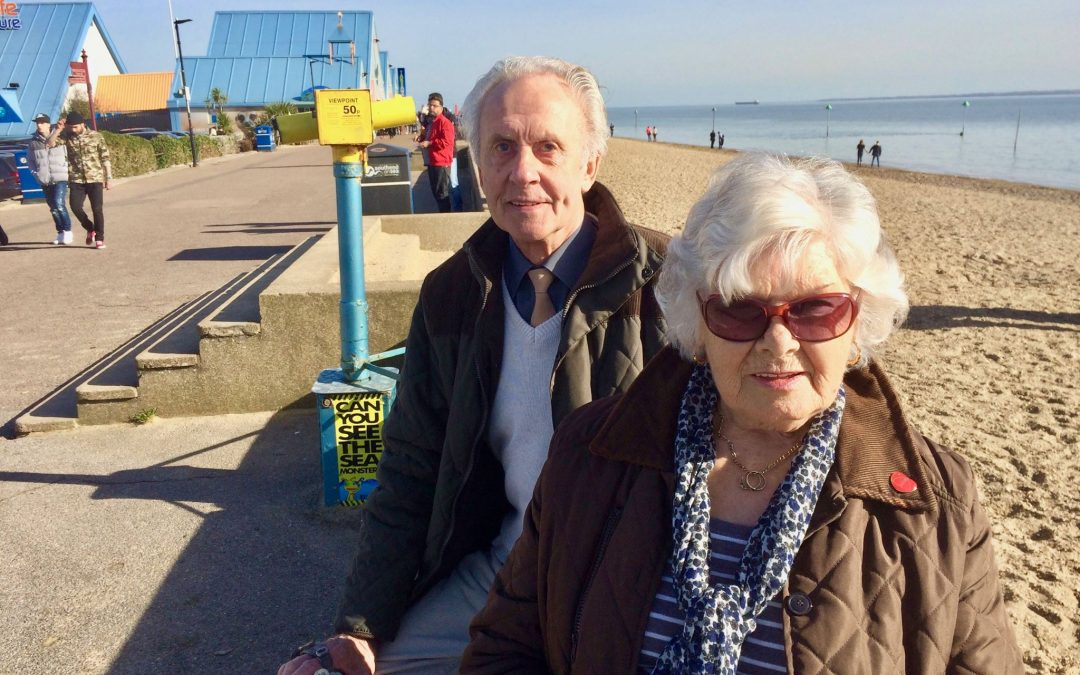 Elderly couple sat by the seaside