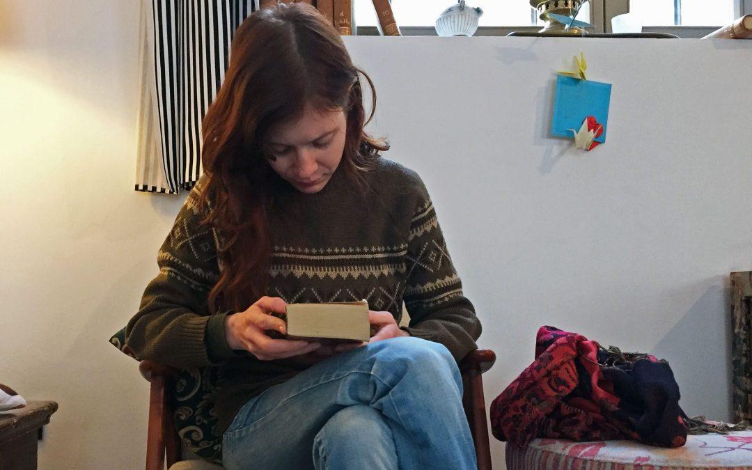 Female human glimpsing down at a book